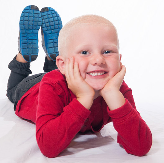 A young boy laying down with his smiling face in his hands at Great Grins for KIDS - Oregon City