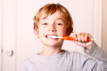 A young boy brushing his teeth with an orange toothbrush.